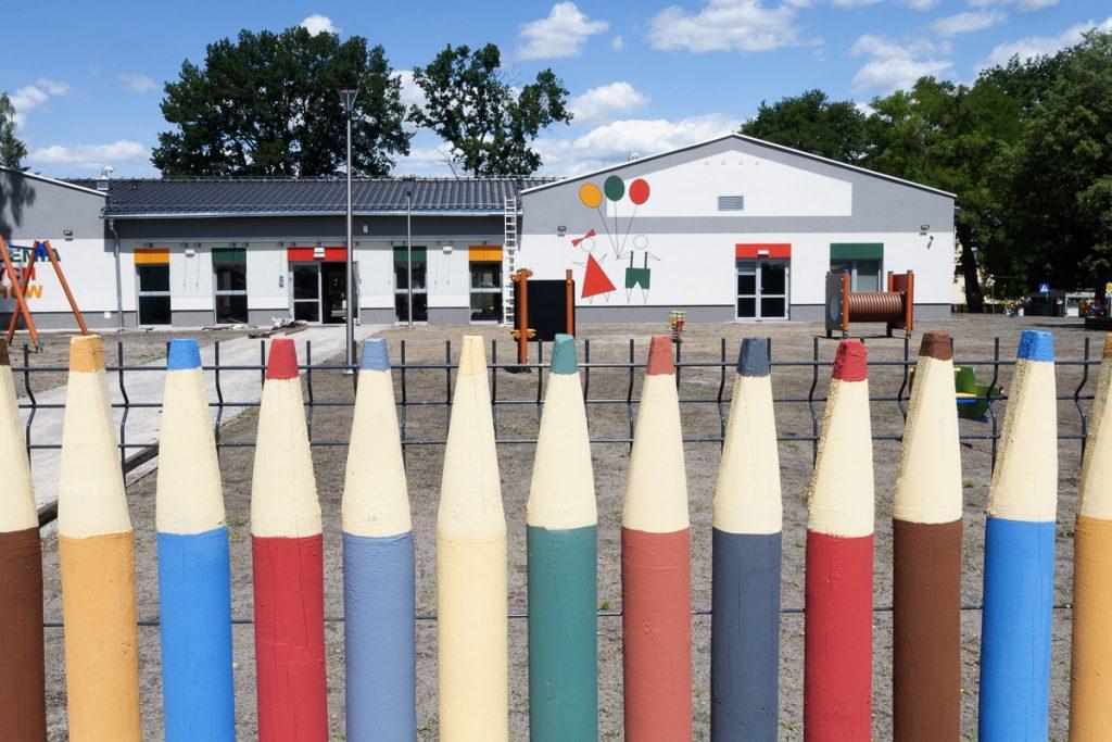 Płot w kształcie kolorowych kredek. W głębi szaro-biały parterowy budynek