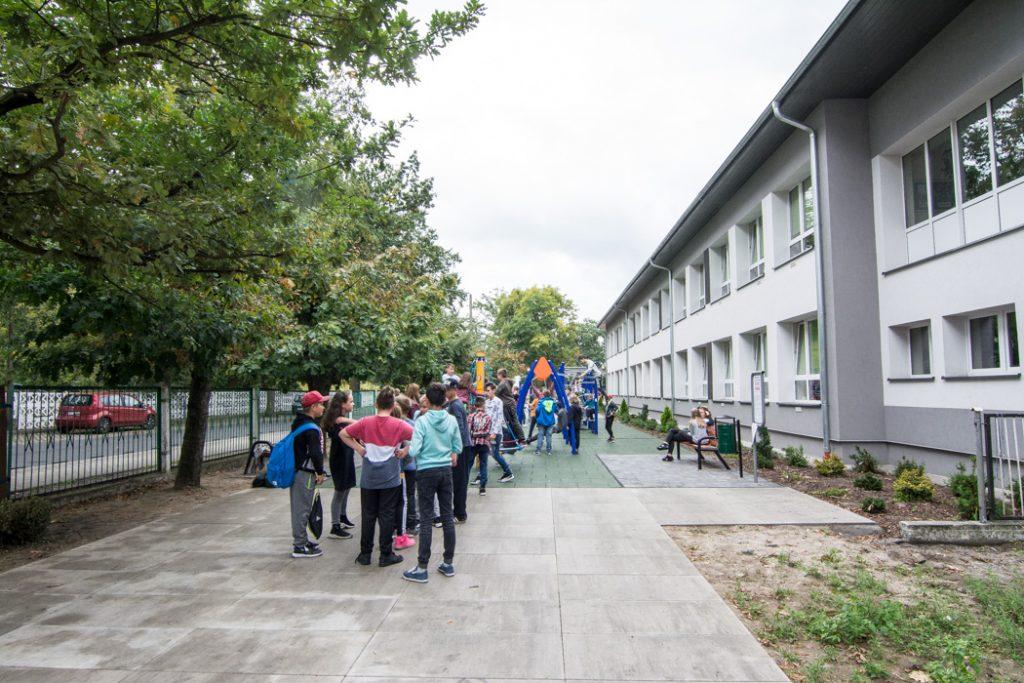 Grupa młodzieży stoi przed budynkiem szkolnym koloru biało-szarego