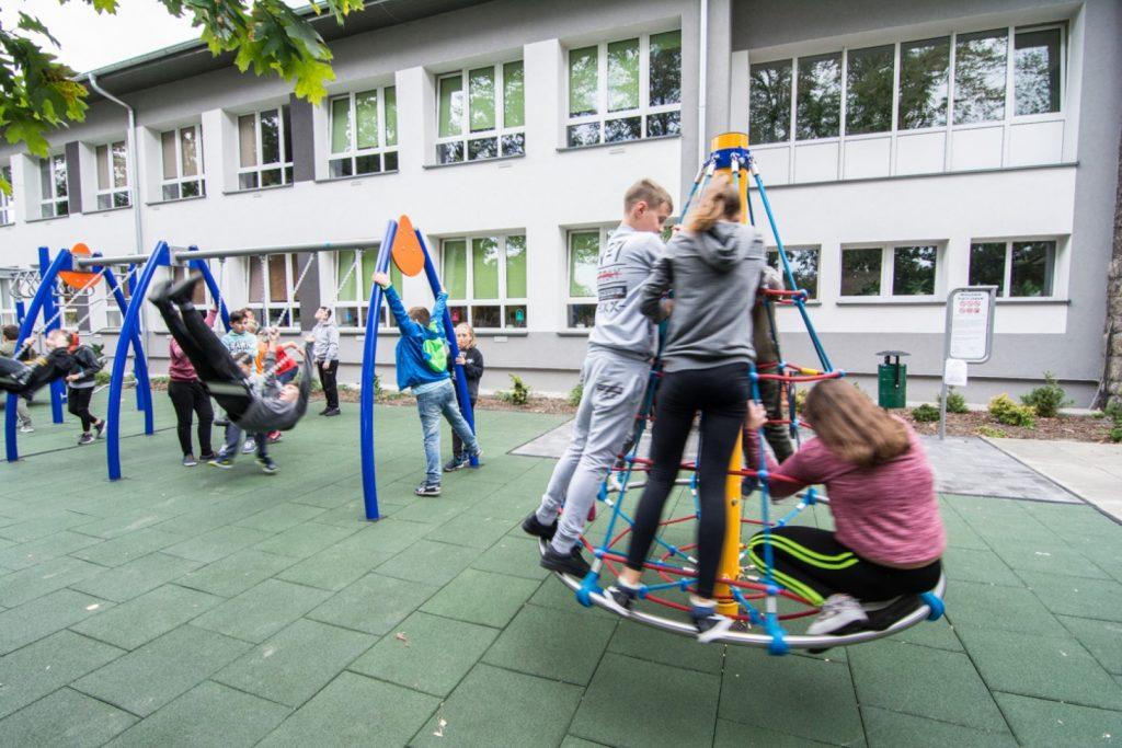 Grupa młodzieży bawi sie na urządzeniach na placu zabaw. W głębi budynk szkolny koloru biało-szarego