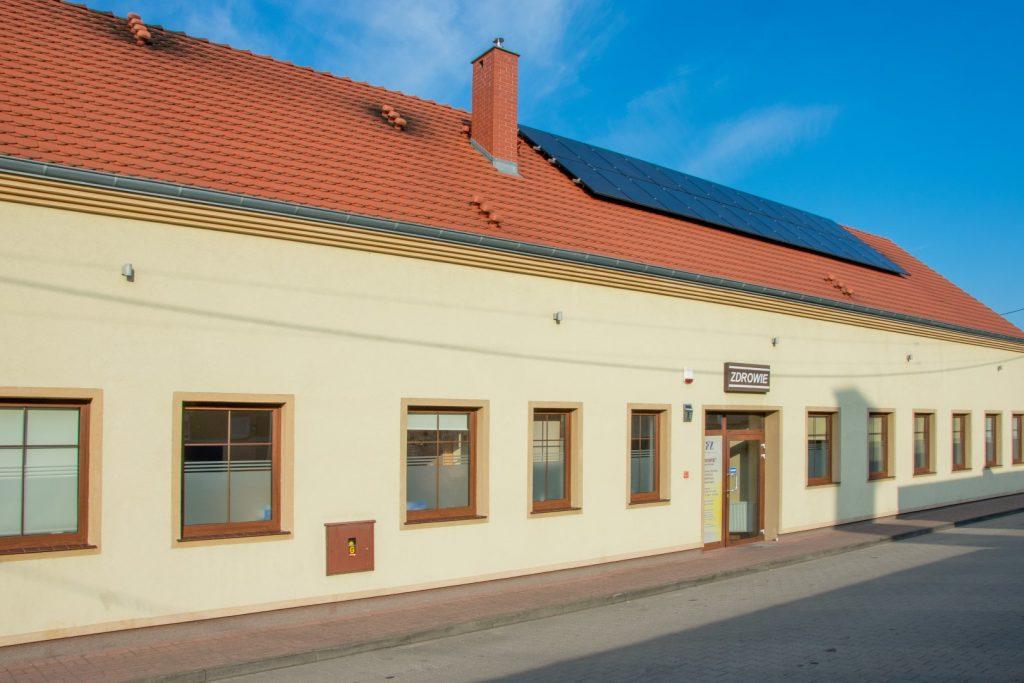 Parterowy budynek koloru pisakowego z czerwonym spadzistym dachem. na dachu panele słoneczne