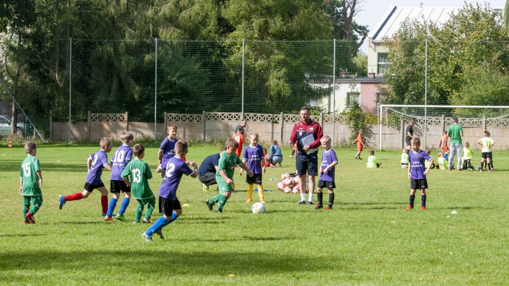 Grupa chłopców odbywa trening piłki nożnej pod okiem mężczyzny w dresie