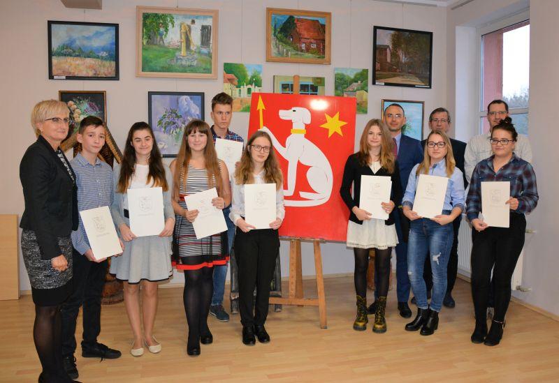 Grupa młodzieży pozuje do zdjęcia i trzyma kartki papieru.