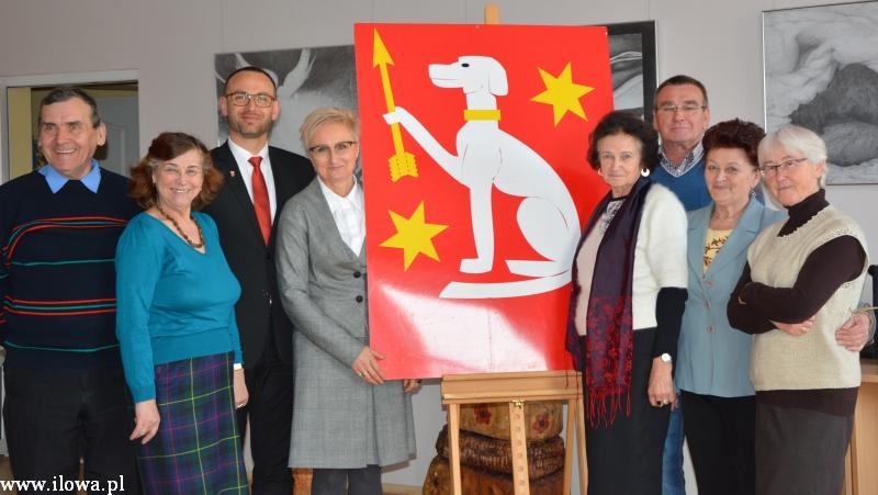 Grupa ośmiu osób pozuje do zdjęcia. Pomiędzy osobami plansza z białym psem trzymającym strzałę i dwoma złotyi gwiazdami