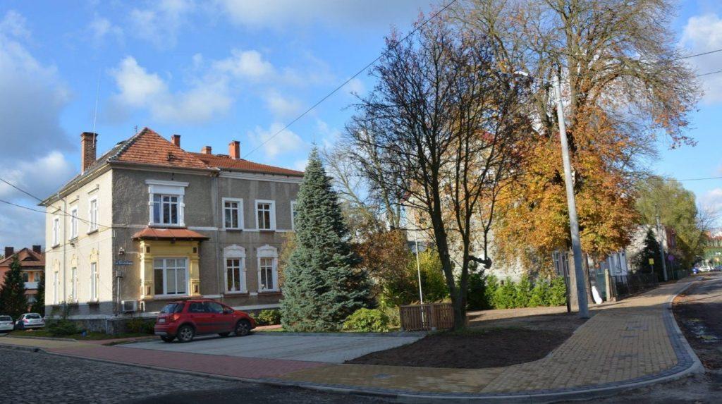 Pietrowy budynek z szarą elewację i czerwonym spadzistym dachem. Przed budynkiem czerwony samochód i drzewa