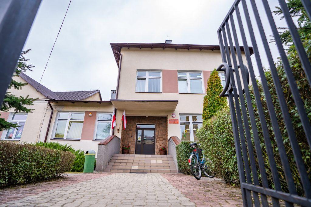 a otwartą brama widać wejście dobudynku szkoły, przy drzwiach wiszą biało-czerwone flagi. Przedwejściem stoi rower
