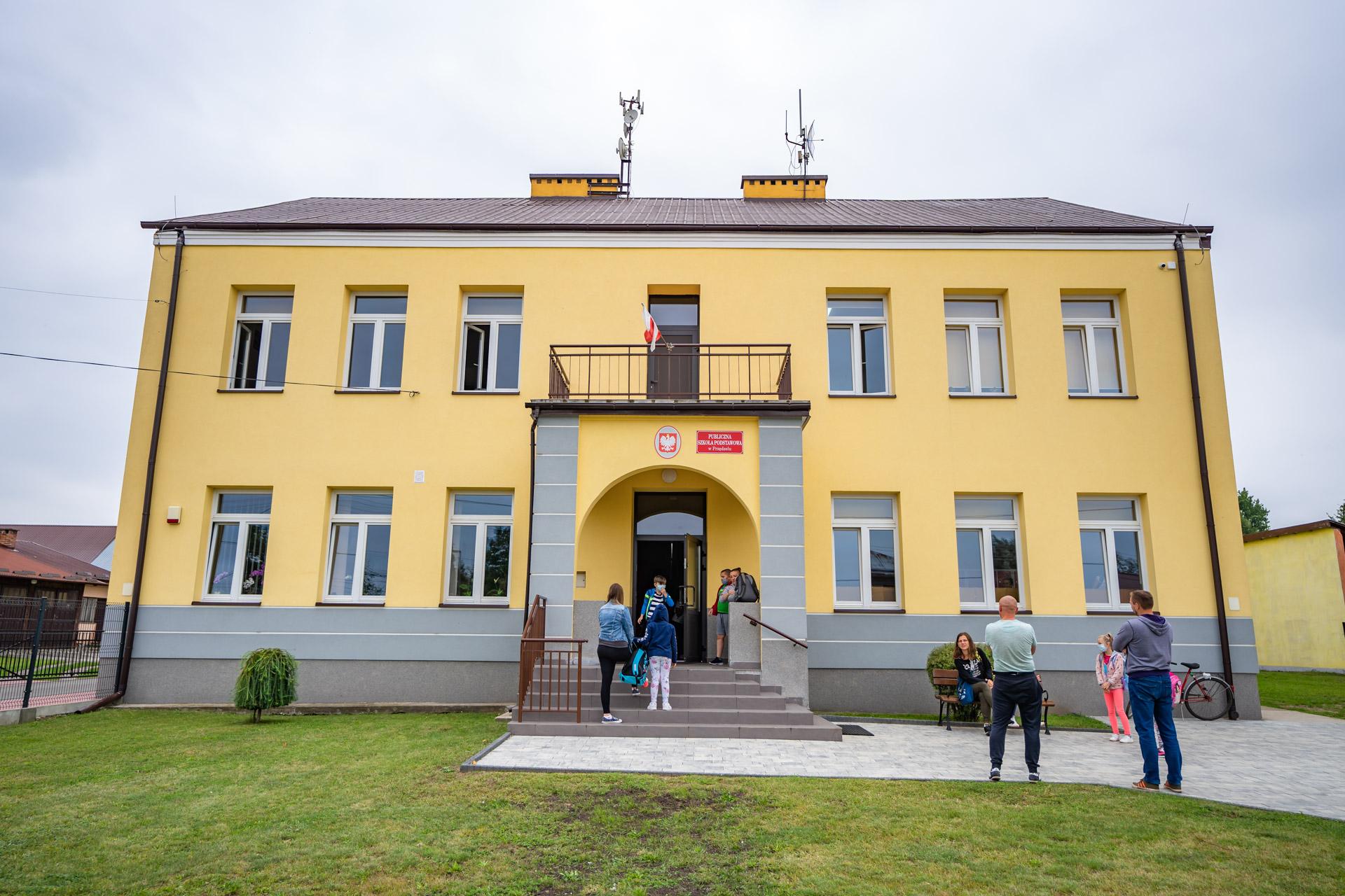 żóto-szary budynek szkoły. Przedszkoła inaschodach młodzież idorośli