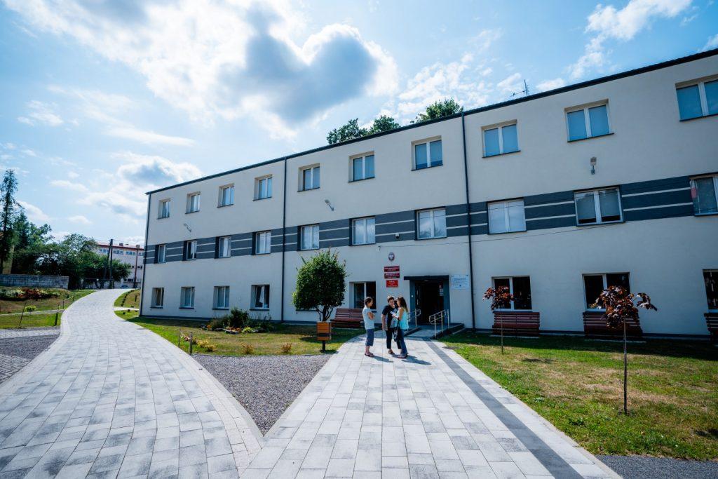 Dwupiętrowy nowy budynek koloru jasnoszarego zgranatowymi pasami biegnącymi przezśrodek obiektu. Przedbudynkiem trawnik odrzewka. Trzy osoby stoja irozmawiają przedgłównym wejsciem