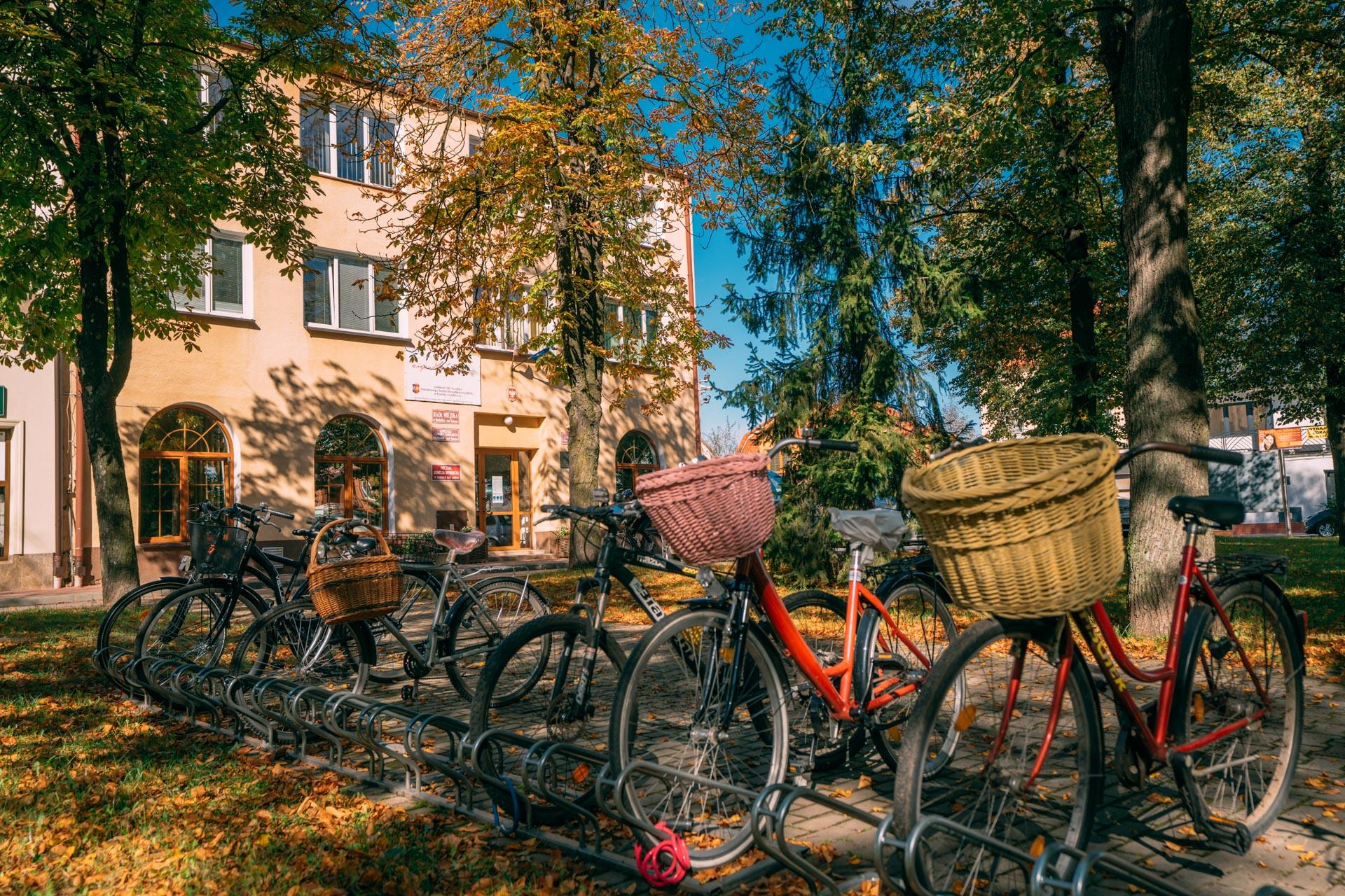 Rowery ustawione nametalowym stojaku przedbudynkiem koloru piaskowego. Dwa rowery czerwone ireszta czarne. Nakierownicach czerwonych rowerów są zamocowane wiklinowe kosze nazakupy