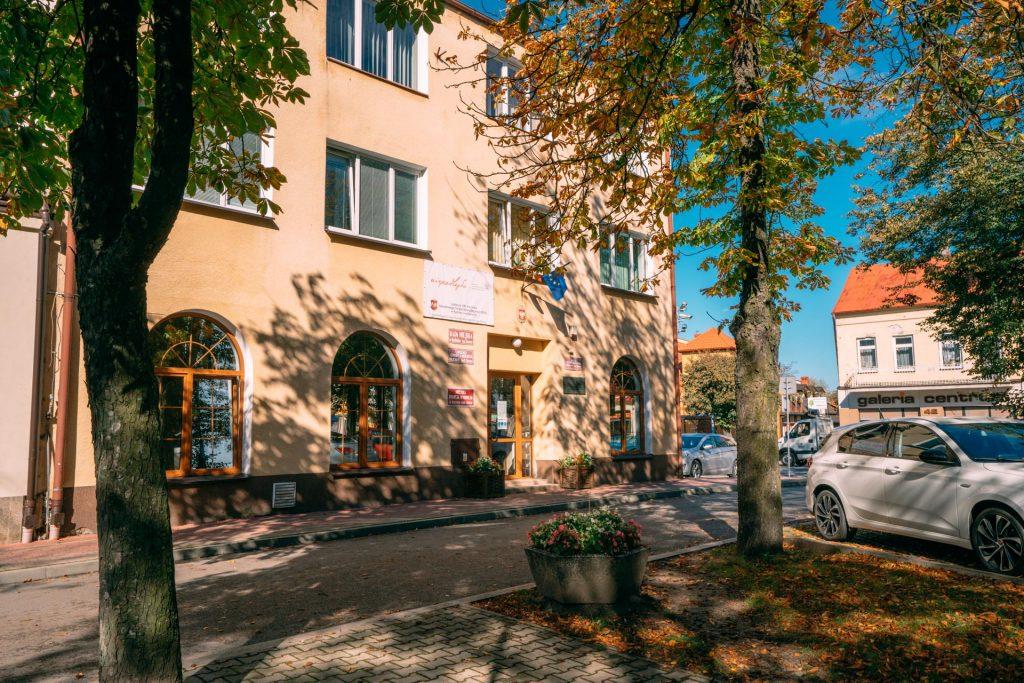 Dwupiętrowy budynek koloru piaskowego, przedbudynkiem dwa drzewa liściaste, naparkingu stoi biały samochód