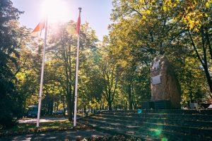 Dwie biało-czerwone flagi powiewają nabiałych masztach, obok duży głaz zmetalową tabliczka imetalowym orłem. Dogłazu prowadzą kamienne schody