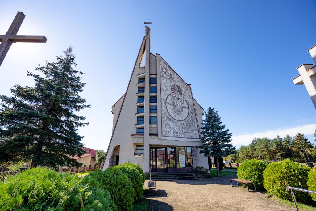 Nowy kościół zjasna elewacją. Nascianie mural. Wokół kościoła zieleń