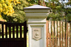 Kamienny słupek ogrodzeniowy zkamiennym herbem, naktórymznajduje sie korona, gwuazda ipółksięzyc