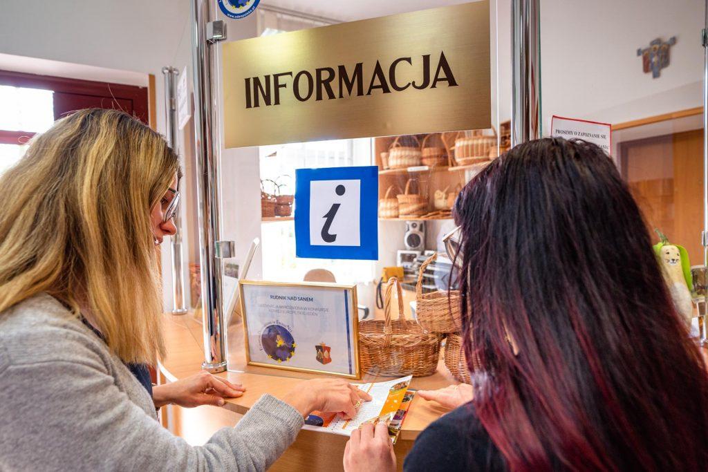 Dwie kobiety zdługimi włosami - jedna blond, druga bordo, stoją przy okienku znapisem Informacja iczytają książkę