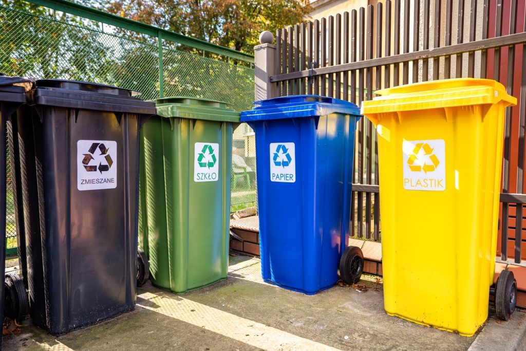 Cztery plastikowe pojemniki naśmieci - czarny, zielony, niebieski iżółty stohą przy płocie