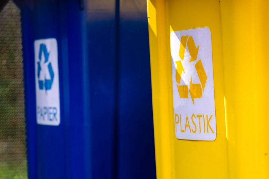 Dwa plastikowe pojemniki - nienieski zbapisem papier iżółty znapisem plastik