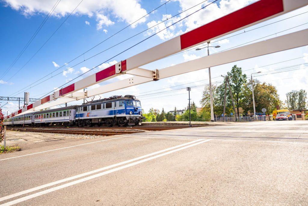 Pociąg pasażerski przejeżdża przezzamknięty przejazd kolejowy. Napierwszym planie zamkniety przejazd