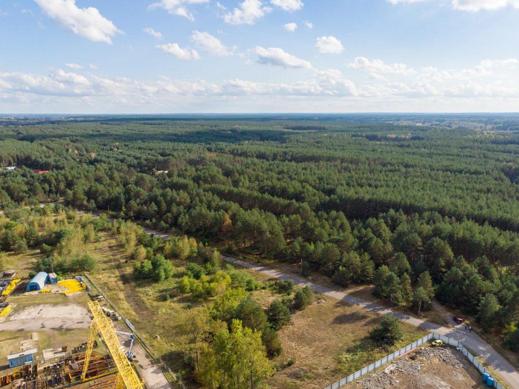 Widok zdrona nazielony las, wlewym dolnym rogu widac żółta konstrukcjemetalową orazbłękitny tunel