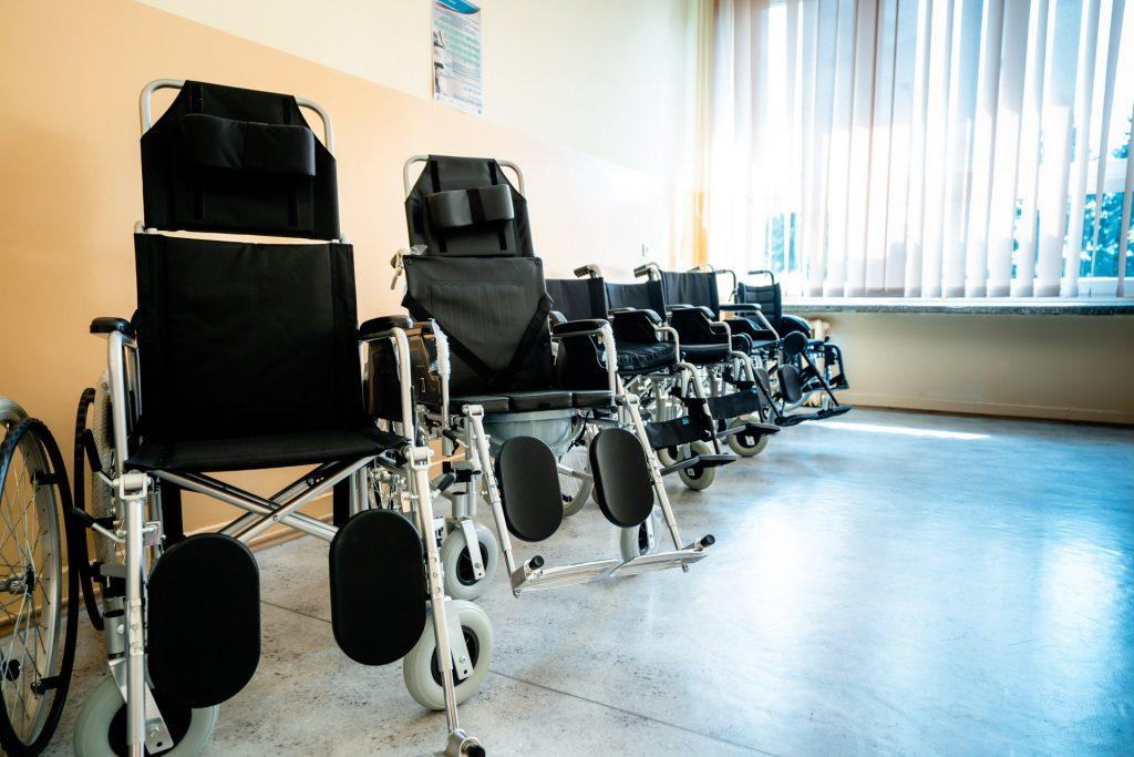 Czarne wózki inwalidzkie zbłyszcącymi stalowymi ramami stoją wrzędzie wzdłuż ściany pomalowanej farbą olejna nakolor piaskowy. Ztyłu duże, zasłonięte okno
