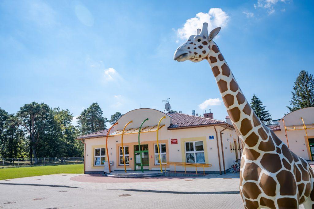 Rzeżba żyrafy w brązowe ciapki. W tle parterowy budynek koloru piaskowego z spadzistym dachem