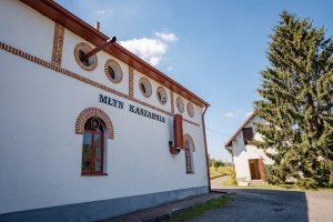 Biały budynek zelekmentami zczerwonej cegły, dwa zookraglona okna iwystająca rura wentylacyjna