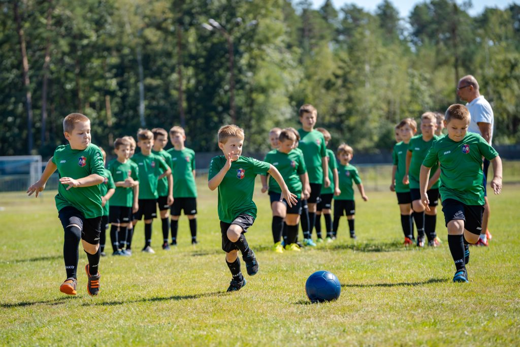 Chłopcy wzielono-czarnych strojach trenują natrawiastym boisku. Zboku stoi mężczyna wgranatowych spodeńkach ibiałej koszulce