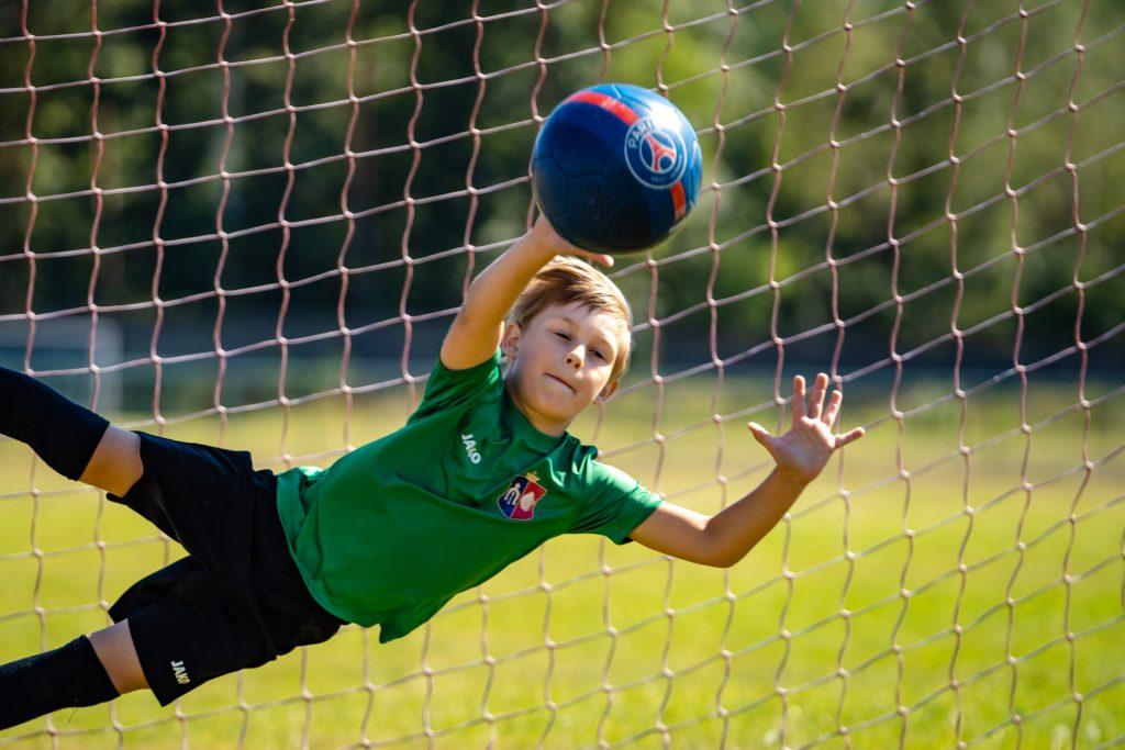 Młody bramlarz wzielonej koszulce iczarnych spodeńkach podczas obrony bramki odbija niebieska piłkę nożną