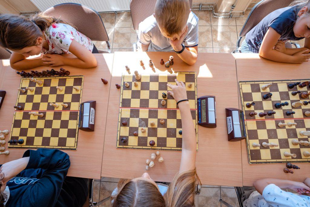 Sześciu młodych szachistów siedzi przy stołach igra wszachy