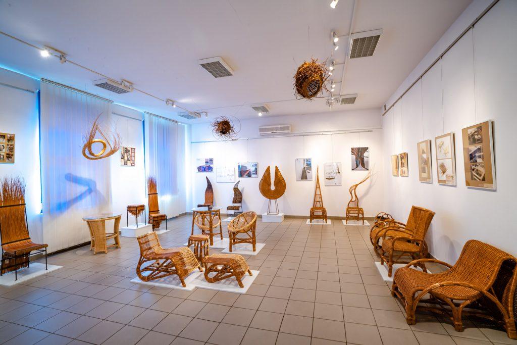 Oryginalne meble iformy zwikliny ustawiony napostumencie wsali wystawowej. Naścianach kolorowe zdjęcia