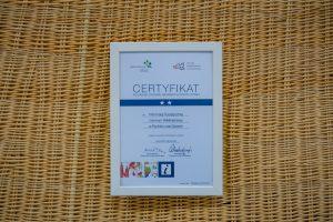 Biało-granatowy certyfikat wbiałej ramce natle wiklinowej ścianki