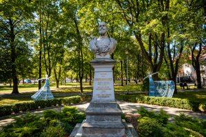 Pomnik mężczyzny zbrodą. Ztyłu dwie rzeźby tancerek wykonane zwikliny pomalowanej nabiało iniebiesko