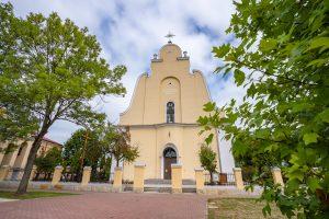 Front kościoła bezwieży ożółtej elewacji. Budynek otoczony płotem idrzewami