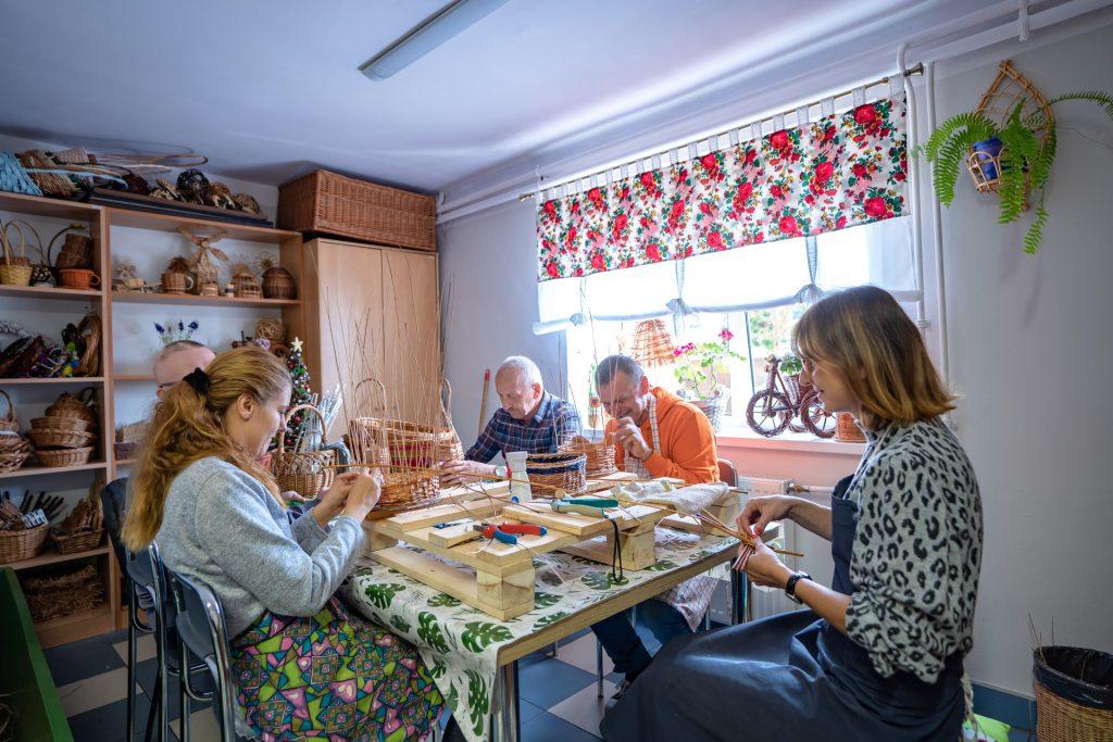 Trzech mężczyzn idwie kobiety siedzą przy stole iwyplatają wiklinowe kosze. Wgłębi półki, ananich wyplecione kosze
