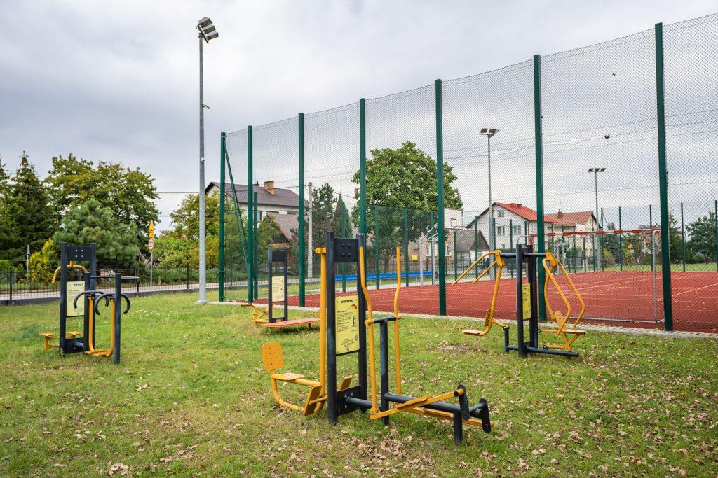 Żółto czarne metalowe urządzenia doćwiczeń fizycznych zainstalowane napodłożu trawiastym obok ogrodzonego boiska