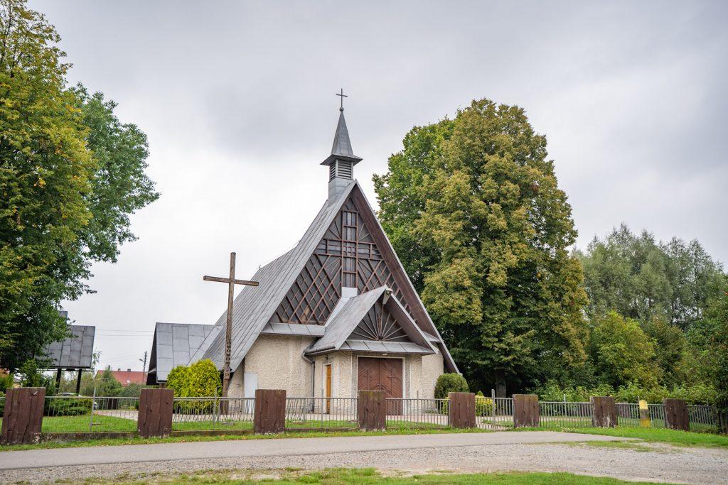 Mały kościółek zespadzistym dachem iportalem zeszkła idrewna. Przy kościele krzyż