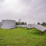 6 rzędów paneli fotowoltaicznych zamontowanych na trawniku. Obok dwa duże okrągłe pojemniki. rukcje połaczone pomostem