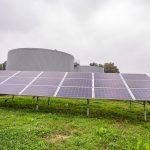 12 paneli fotowoltaicznych zamontowanych na trawniku. Za panelami szare, okrągłe konstrukcje połaczone pomostem
