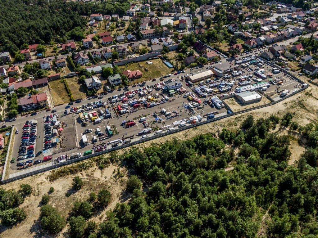 Zdjęcie dużego placu z lotu ptaka. Na placy dużo samochodów i budynki. W pobliżu placu drzewa i zabudowa mieszkaniowa