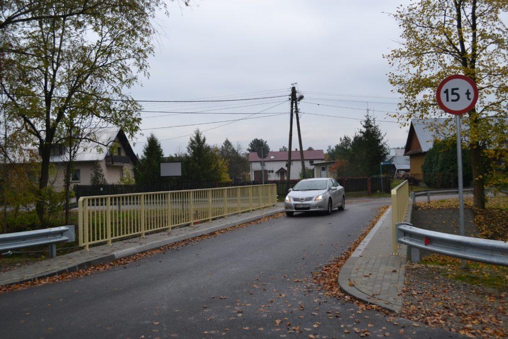 Na most wjeżdża srebrny samochód zzapalonymi światłami. Poobu stronach mostu wybrukowany chodnik iżółta balustrada. Przedmostem znak drogowy