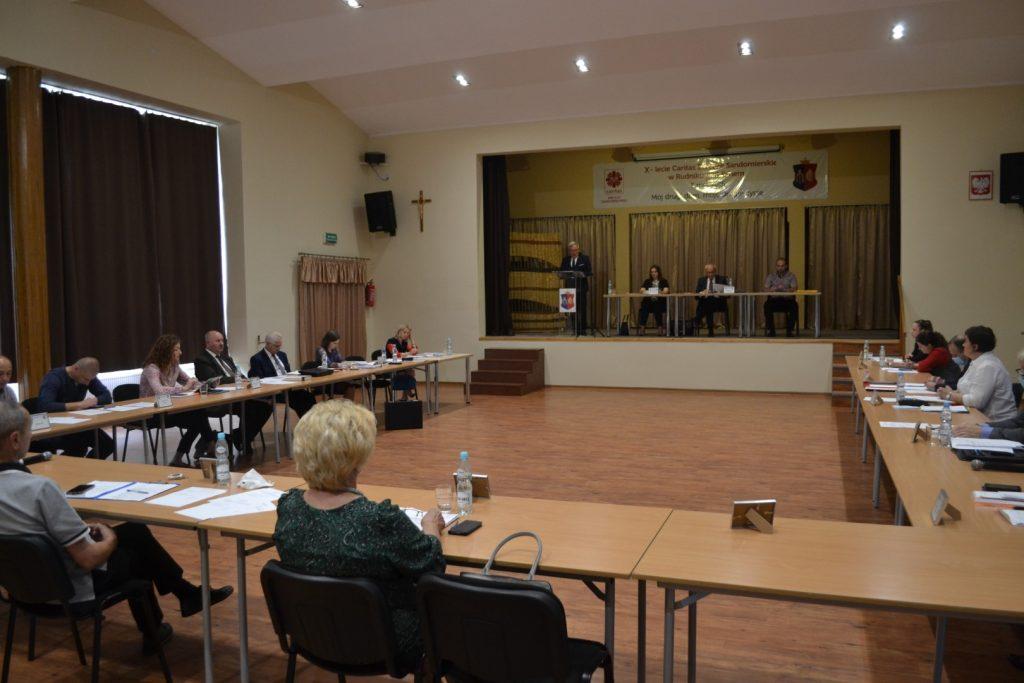 Grupa osób siedzi przy stole wkształcie litery U. Nascenie stół, aprzy nim siedzą trzy osoby. obok mównica zprzemawiającym mężczyzną.