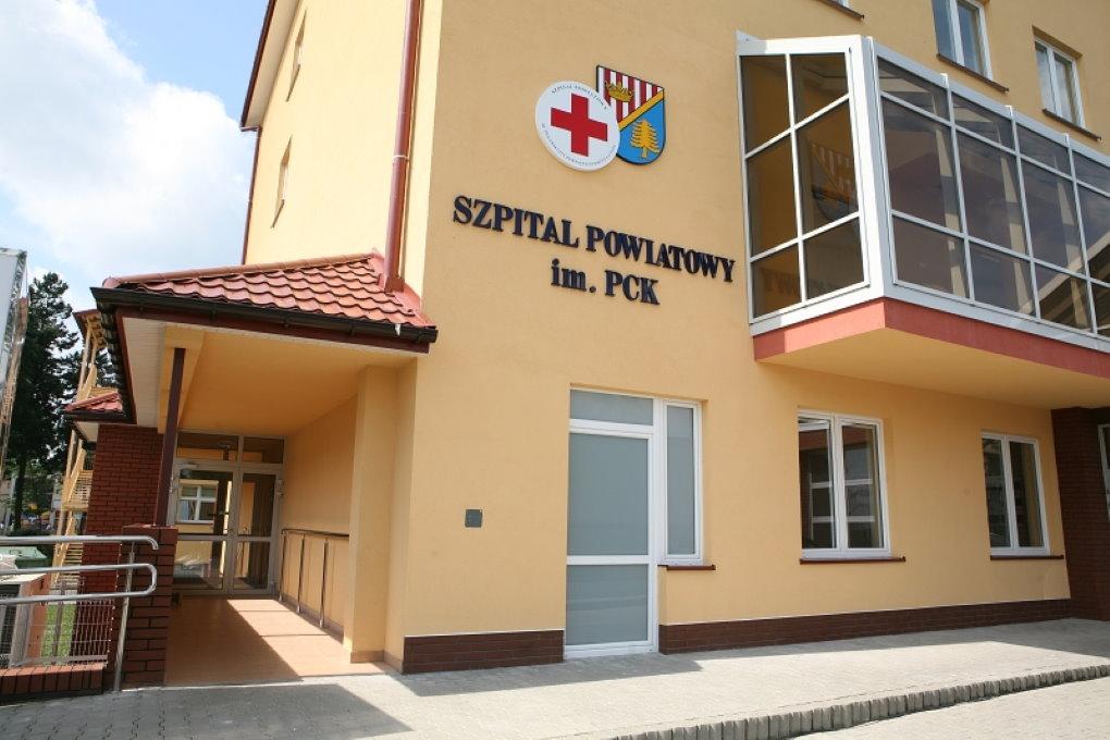 Budunek koloru piaskowego znapisem Szpital Powiatowy im.PCK. Zboku zadaszone główne wejście zpodjazdem dla osób niepełnosprawnych