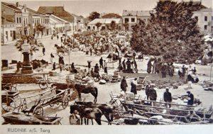 Stara pocztówka czarno-biała przedstawiająca targ. Widać zaprzęgi konne, wozy drabiniaste
