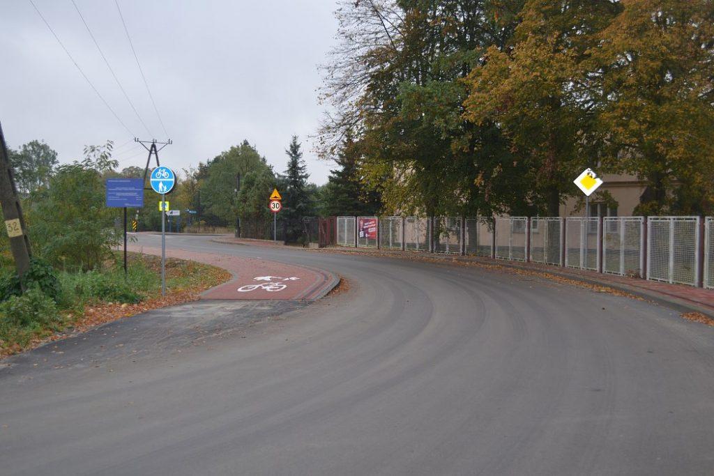 Wyasfaltowana ulica wchodząca wzakręt wlewo. Wzdłuż prawego boku drogi wybrukowany chodnik koloru czerwonego ipłot, wzdłuz lewego boku chodnik iścieżka rowerowa wyłozona czerwonym brukiem